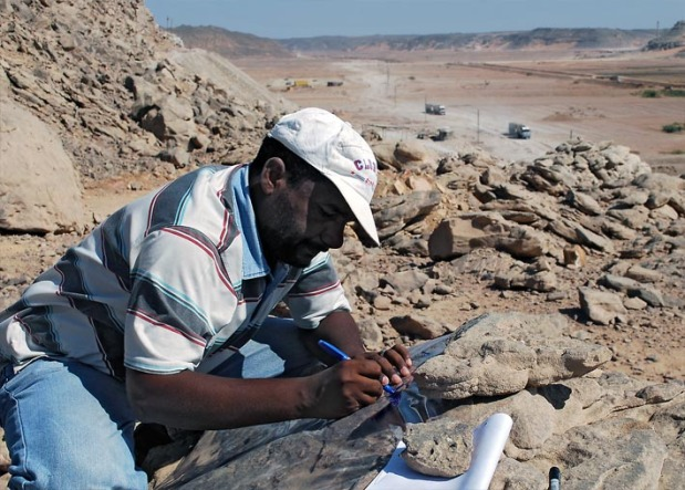 Adel Kamel of the Supreme Council of Antiquities in Aswan recording Late Palaeolithic rock art while heavy trucks are transporting clay for the Egyptian ceramics industry in the background. Photo: Per Storemyr