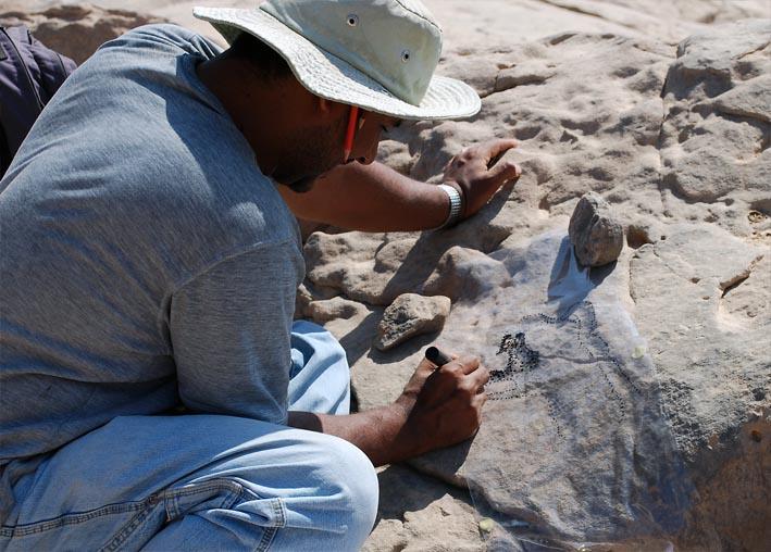 Adel Kelany recording a Late Palaeolithic petroglypph: Photo: Per Storemyr