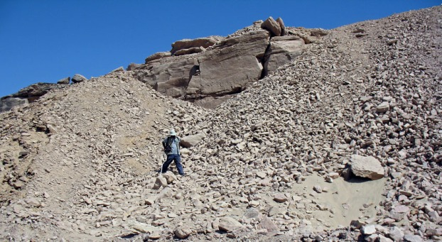 Rock art (on the cliff) among spoil heaps from modern stone quarrying in Wadi Abu Subeira: Adel Kelany on his way down from inspecting part of rock art site CAS-7 (Pharonic rock art). Photo: Per Storemyr