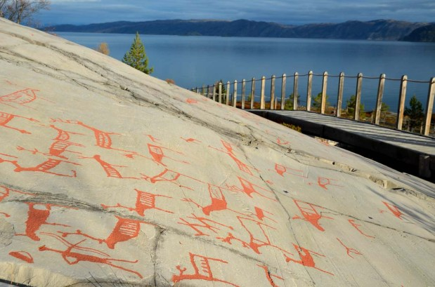 Reindeer hunter with bow and arrow (low, left) in the prehistoric Alta rock art. Photo: Per Storemyr