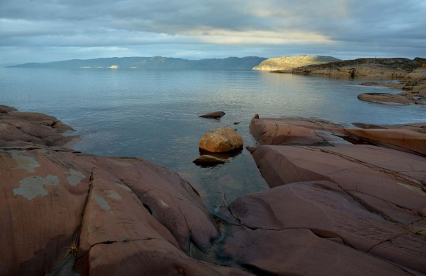 The current shoreline in at Alta, with reddish patinated bedrock. The surface features of the rock is otherwise a result of ice-scouring during the last Ice Age. The natural colour of the rock can be seen in the areas with exfoliation. Photo: Per Storemyr