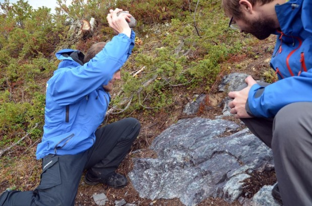 Was it like this the chert at Melsvik was quarried in the Stone Age? Archaeologist Lars Julsrud of Alta Museum applying brute force with a hammerstone (without touching the ancient surface!), his colleague Martin Hykkerud perhaps taking a more sceptic stance. Photo: Per Storemyr