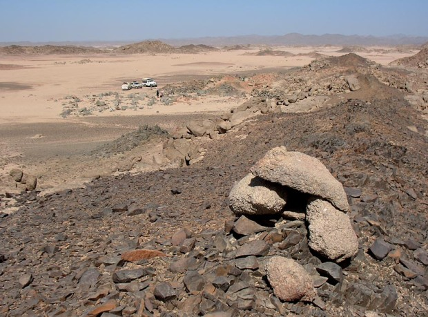 Volcanic dyke at Rod el-Gamra showing signs of exploitation by Palaeolithic man. The naoi quarry is in the background. Photo: Per Storemyr