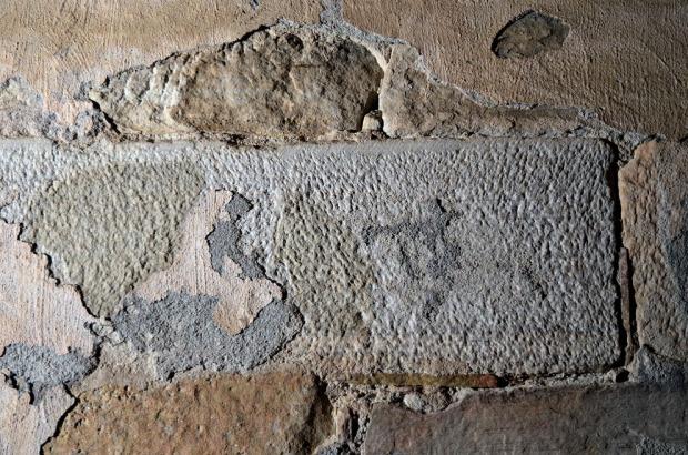 """Overflatebearbeiding av finbåndet, lys marmorkvader innvendig i korets østgavl. Merk """"slaget"""" på oversiden og den """"fingropete"""" overflaten. På bildet kan man også se detaljer i gavlen puss, med en tynnpuss under (grålig) og slemming over, der sporene etter kalkkosten er godt synlige. Foto: Per Storemyr"""