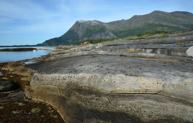 Flott, båndet platemarmor langs fjæra rett nord for Gildeskål kirke (Stokkbruvika). I bakgrunnen Sandhornet. Foto: Per Storemyr