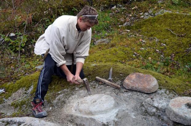 Roy Harald Brendsdal hogger dreiekvern etter vikingtidens mønster i Hyllestad. Foto: Per Storemyr
