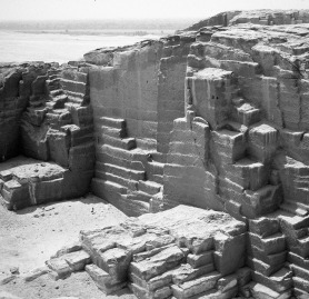 Multiple-block extraction on descending platforms in the New Kingdom to Late Period part of the el-Sawayta limestone quarry near Samalut. Note the wide, shallow steps left by offset platforms and, at center and at left, the two narrower but deeper, squarish platform remnants. Photo by JAMES HARRELL.