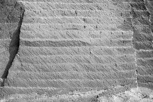 Platform extraction levels on the wall of the Roman Nazlet Hussein Ali limestone quarry near el-Minya. Note the regularly spaced, vertical gashes left at each platform level representing block widths. Photo by JAMES HARRELL.