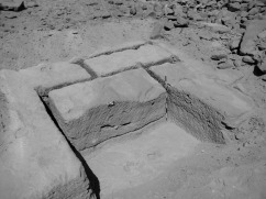 Partially extracted blocks in the Ramesside (19th-20th Dynasties) part of the Gebel el-Silsila sandstone quarry. Note the two parallel grooves at the back of the leftmost trench. Smallest scale divisions are 1 cm at center and 10 cm at right. Photo by JOHN WARD.