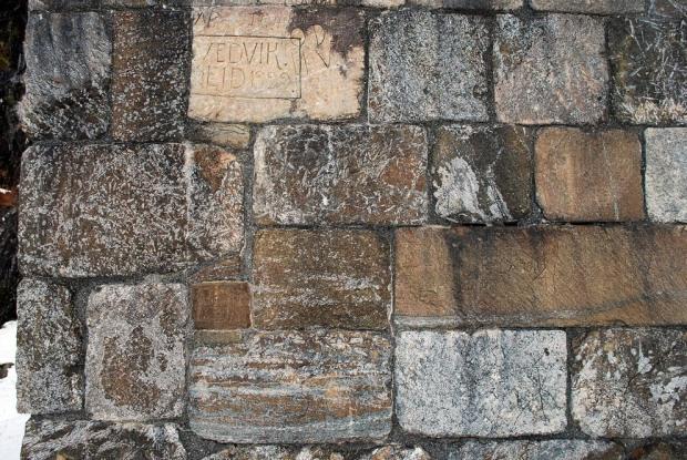 Typisk varierende utseende på metaolivinstein på Selja, her fra det rekonstruerte murverket på ruinen av Sunnivakirken. De lyse partiene er talkrike, de brune er olivinrike. Den brune fargen skyldes forvitring; opprinnelig var steinen nesten grønn. Foto: Per Storemyr