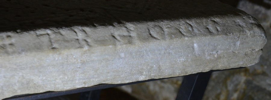 Detalj av gravplaten fra 1200-tallet som nå befinner seg i søndre sidealternisje i Værnes kirke. Gravplaten er hogd i hvit marmor med karakteristiske «bånd» av mørkere mineraler. Platen kommer etter all sannsynlighet fra Nidarosdomens gamle brudd i Sparbu. Foto: Per Storemyr.