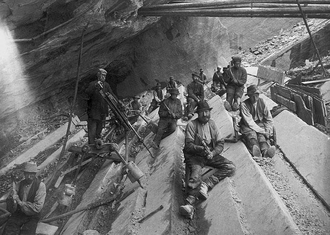 Fra skiferbruddet ved Skarsjøen, et av de mange bruddene som var i drift i Stjørdal fra midten av 1800-tallet og utover. Steinbryterne hogger lange kanaler på tvers av kløven i skiferen, som så blir kilt ut som plater. En tidlig boremaskin har kommet på plass, men akkurat her er den satt opp kun for å vises frem. Ukjent fotograf, ca. 1900. Fra Pettersson 1999.