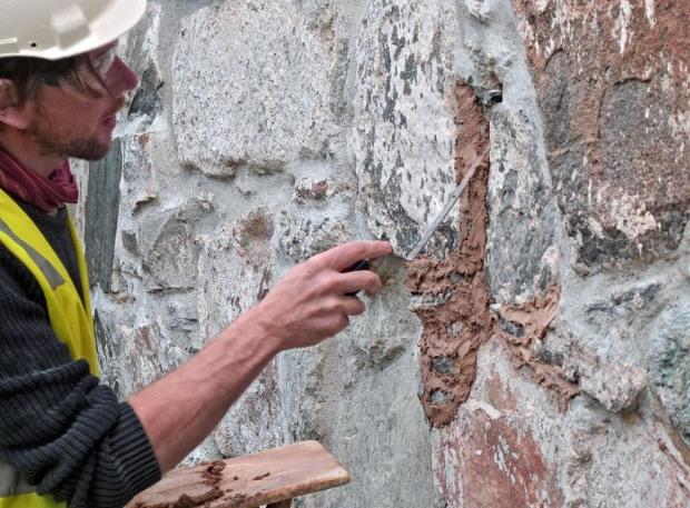 George Murphy er spesialist på restaureringsmuring. Her tester han mørtel laget fra nybrent Hyllestadkalk på Stavanger domkirke i oktober 2017. Foto: Per Storemyr