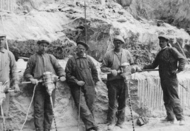 SØMBORING: Kleberarbeidere med bormaskiner, trolig i Bårstadbruddene ved Lalm på 1920-tallet. Til høyre ses sømboring i bergveggen. Foto gjengitt med tillatelse av Sel Historielag, se deres fotosamling.