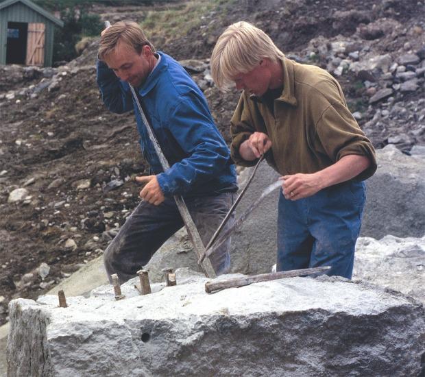 SPLITTING: Steinhoggerne Atle Elverum og Henning Grøtt deler opp blokk ved hjelp av kiler med blekker i kleberbruddet på Bubakk ved Kvikne i 1995. Dette var et av de aller siste steinuttakene i bruddet. Foto: Per Storemyr