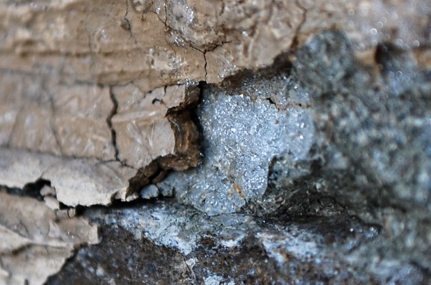 Frost heaving in masonry III: A thin lens of ice has formed below lime plaster, breaking it loose. More pieces to follow! Masonry of limekiln in Hyllestad, Western Norway. Width of image c. 5 cm. Photo by Per Storemyr