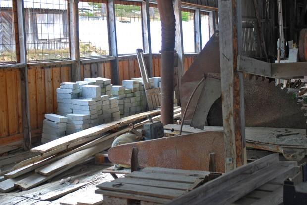 I saghuset på Sagflaten: Sirkelsag, rustet avsug og i bakgrunnen et forlatt lager med kleber som var ment for ildfaststein. Foto: Per Storemyr (2018)