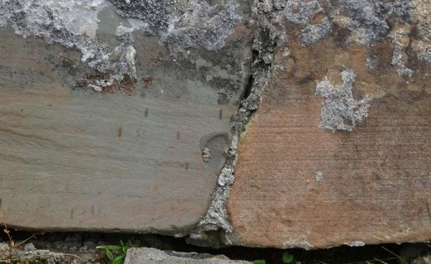 """Devonsandsteinen på Kinn kirke. Til høyre: """"Rustet"""", naturlig overflate med isskuringsstriper. Til venstre: Splittet overflate med """"frisk"""", grønnlig farge. Foto: Per Storemyr"""
