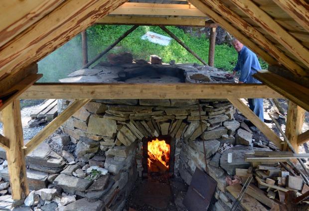 Eksperimentell kalkbrenning i en nedskalert, fri kopi av en middelalderovn, Kvernsteinsparken i Hyllestad. I denne ovnen når man mer enn 1200 grader i bakkant og bare 7-800 grader i framkant. Foto: Per Storemyr.