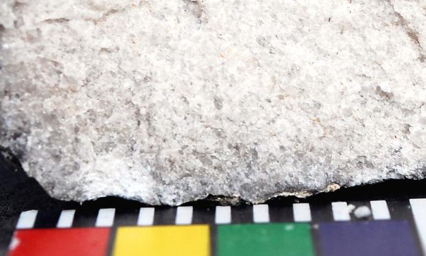 Makrofoto av en ubrent marmorbit fra den romanske delen av Albanuskirken. Marmoren er finkornet, kornstørrelsen er stort sett mindre enn 1 mm (mm-skala i forkant). Foto: Per Storemyr