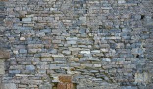 """Sterkt forbrent romansk murverk med murestein på østfasaden av Albanustårnet. En aner en trekant i muren; den viser gavltrekanten på den nå ruinerte Albanuskirken. Legg merke til at trekanten har finlaminert gneis, mens øvrige deler domineres av """"øyegneis"""". Foto: Per Storemyr"""