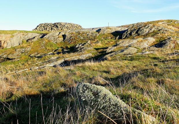 Stumpen av Sonkakrossen. En lavbevokst stein i fremkant, ikke langt fra ei svær gravrøys fra bronsealderen. Foto: Per Storemyr