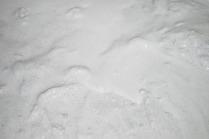 """Ferdig lesket, hvit Smillakalk. Vi ser mange små mørke korn. Dette er mineraler som (brent) glimmer og amfibol; Smillakalk er uren - og disse mineralene vil gi kalken et """"tradisjonelt preg"""". Foto: Per Storemyr"""