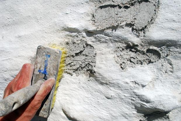 Feit kalkmørtel blandet som hotmix er kastet på de frostskadde områdene og skures hardt inn med kost.