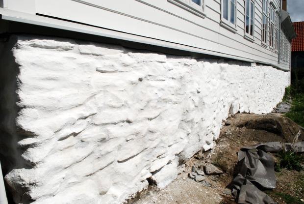 Nær ferdig behandlet mur med kalkreparasjoner og hvitting. Det gjenstår et strøk eller to med hvitting i de nærmeste delene