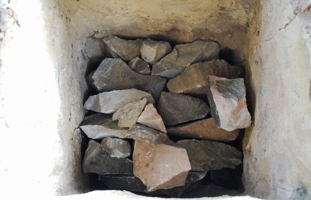 Fylling av Vesleovnen starter med bygging av et enkelt tønnehvelv. Så følger ilegg av marmor, biter på størrelse med to-tre knyttnevner nede, mindre mot toppen. I hvert hjørne bygges det inn trekkanaler