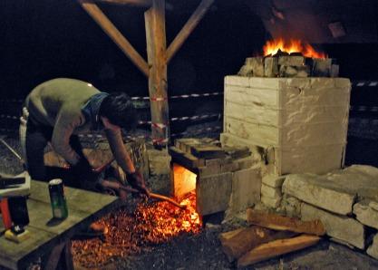 Litt kull og aske tas ut for å få mer futt i ovnen